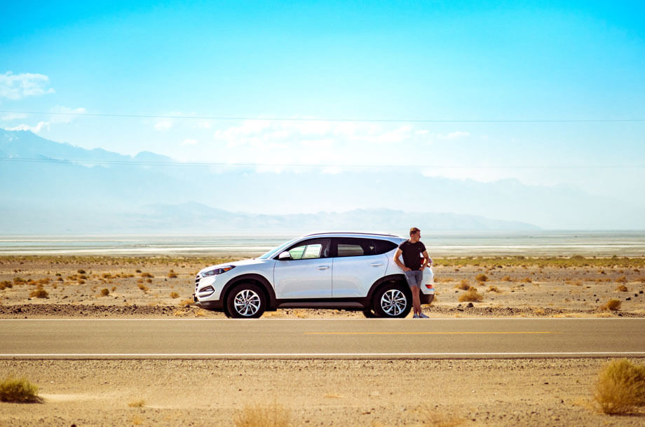 Man standing on side of road with car photo | Thompson Insurance | Auto Insurance